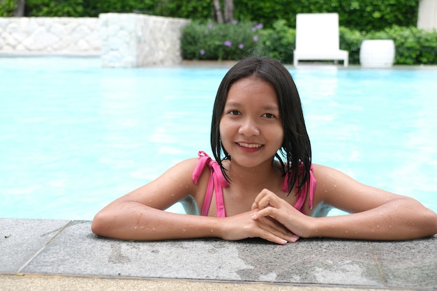 スイミングプールで笑っている若い女の子