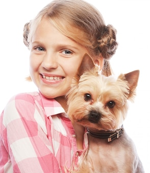 Young girl smiling holding a cute puppy