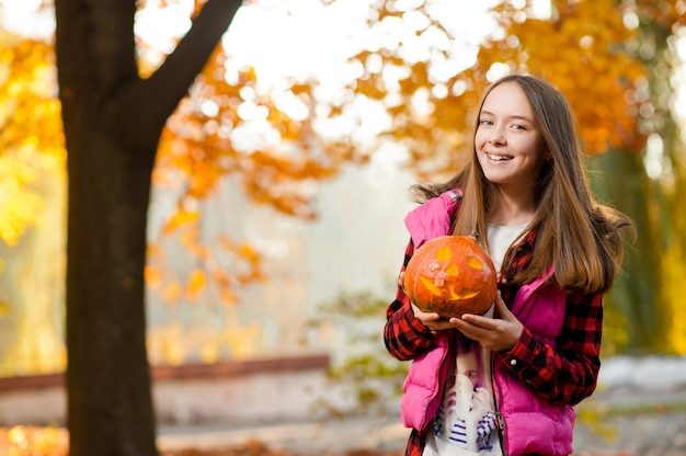 Young girl smiling joyfully with a pumpkin in her hands