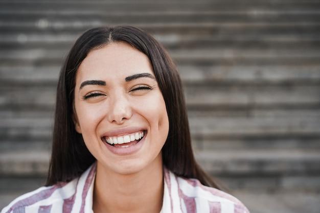 街の屋外で楽しんでいるカメラに微笑んでいる若い女の子-顔に焦点を当てる