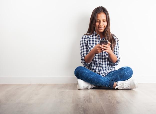 若い女の子が笑顔携帯電話で床に座って