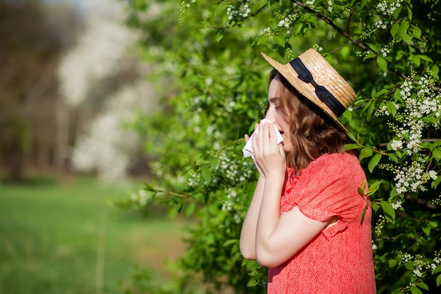 Young girl sneezing in tissue in front of blooming tree