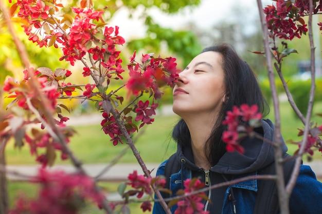 Молодая девушка нюхает цветы с розовыми лепестками на прогулке в парке