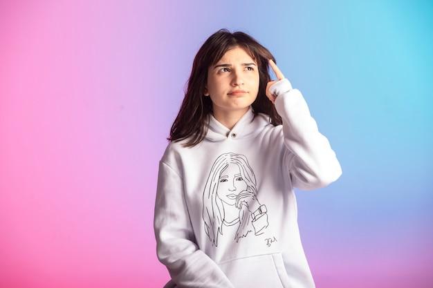 Giovane ragazza in abiti sportivi e acconciatura corta pensando attentamente.