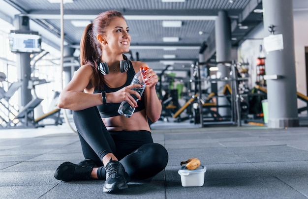 Young girl in sportive clothes taking a break with food and water is in the gym at daytime.