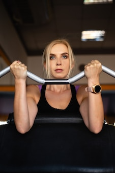 A young girl in the sports hall is engaged, strong hands lift the barbell with weight, a focused look and achievement of goals.