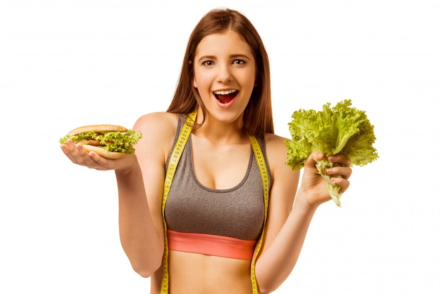 Young girl in sportswear, choice of salad and sandwich.