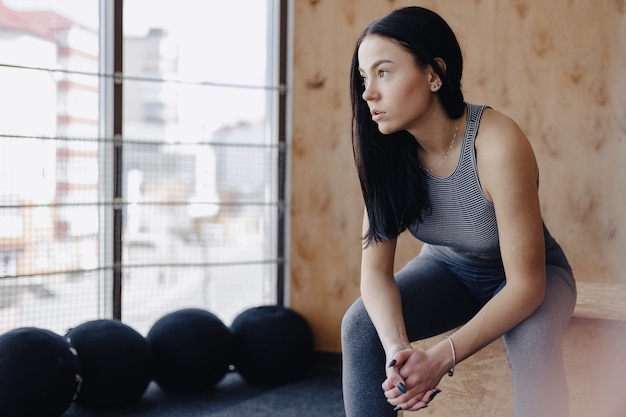 Young girl in sportswear in a gym in a simple background, a theme of fitness, a crossfit and sport