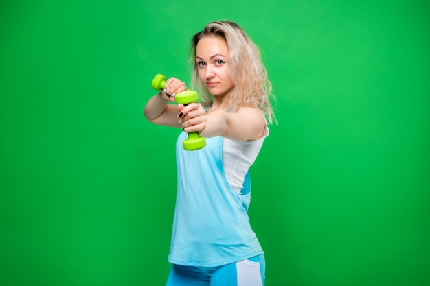 Young girl in sportswear holding dumbbells on a green wall, space for text