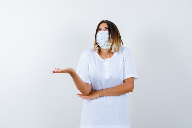 Giovane ragazza allargando il palmo da parte, tenendo la mano sotto il gomito in maglietta bianca, maschera e guardando pensieroso. vista frontale.