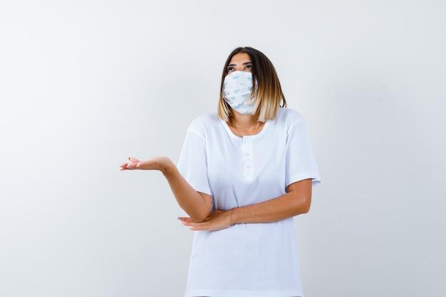 Молодая девушка разводит ладонь в сторону, держит руку под локтем в белой футболке, маске и выглядит задумчиво. передний план.