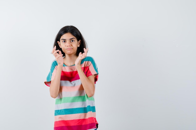 Young girl spreading palms out in colorful striped t-shirt and looking cute , front view.