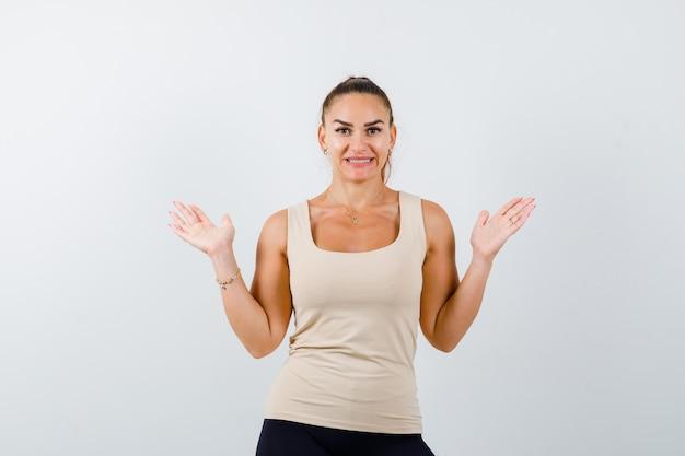 ベージュのトップ、黒のズボンと幸せそうに見える喜びで手のひらを広げている若い女の子