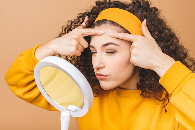 Young girl squeezes pimple on the fer face in front of a bathroom mirror. beauty skincare and wellness morning concept isolated over beige background.