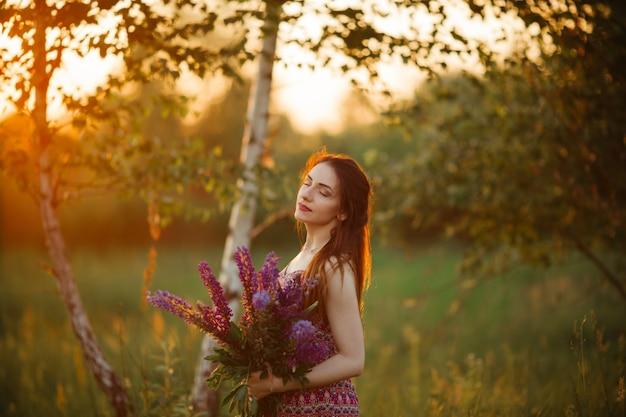 라벤더 밭을 내려다 보이는 필드에 어린 소녀 스탠드. 드레스를 입고 석양을 즐기는 평온한 백인 소녀 미소