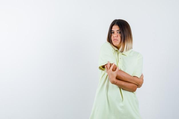 어린 소녀 서 팔 넘어, t- 셔츠에 팔꿈치에 손을 잡고 예쁜 찾고. 전면보기.