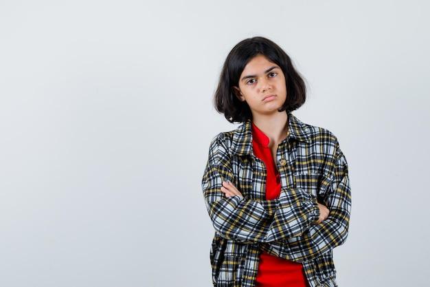 체크 셔츠와 빨간 티셔츠를 입고 팔짱을 끼고 진지한 표정으로 서 있는 어린 소녀. 전면보기.