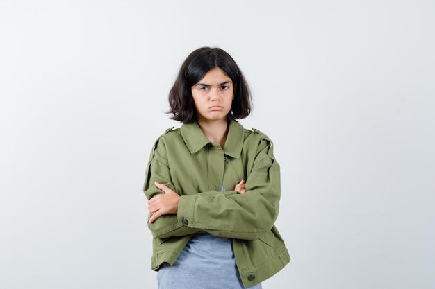 회색 스웨터, 카키색 재킷, 진 바지를 입고 팔짱을 끼고 진지하게 보이는 어린 소녀. 전면보기.