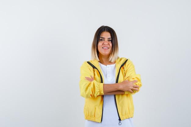 腕を組んで立っている若い女の子、白いtシャツ、黄色のジャケットに笑みを浮かべて、陽気に見える、正面図。