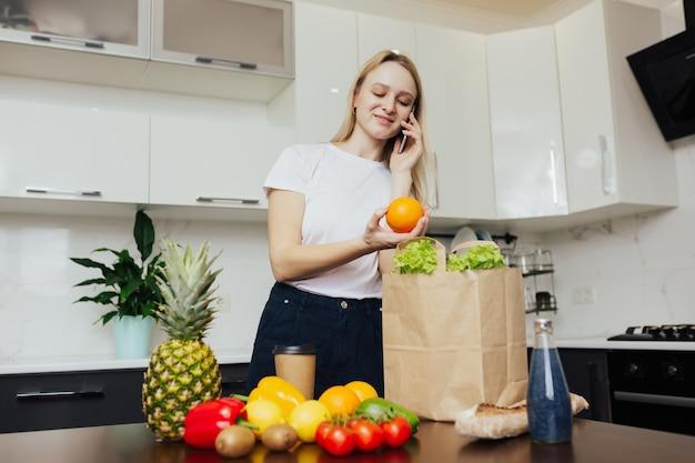 Молодая девушка стоит на кухне, разговаривает по телефону и смотрит на овощи и фрукты в бумажном пакете на столе.