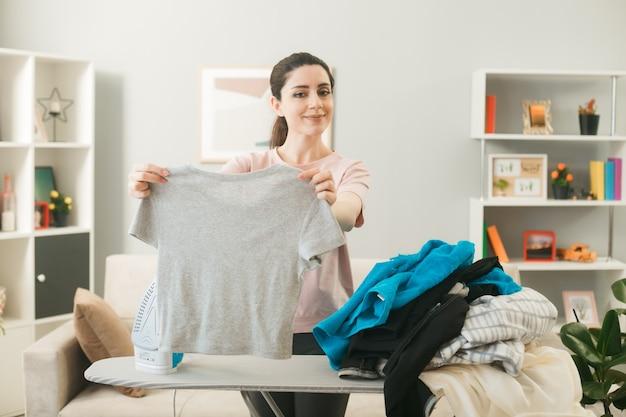 거실에 옷을 입고 다림판 뒤에 서 있는 어린 소녀