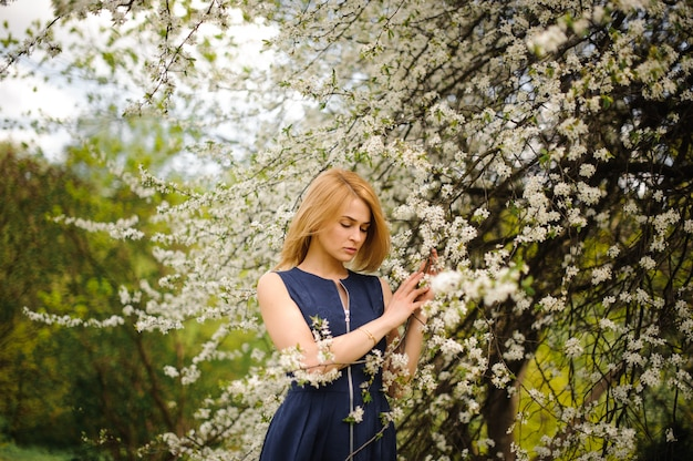 Young girl standing between branches of white blossom tree
