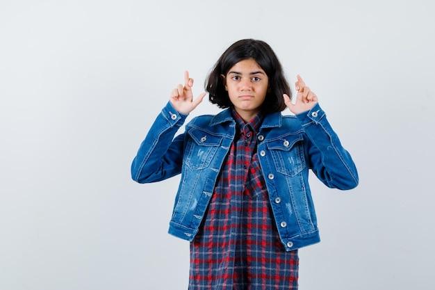 체크 셔츠와 진 재킷을 입고 서 있는 어린 소녀가 진지한 표정으로 손가락을 건넜습니다.