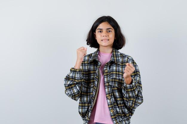 チェックシャツとピンクのtシャツでボクサーのポーズで立って怒っているように見える若い女の子。正面図。
