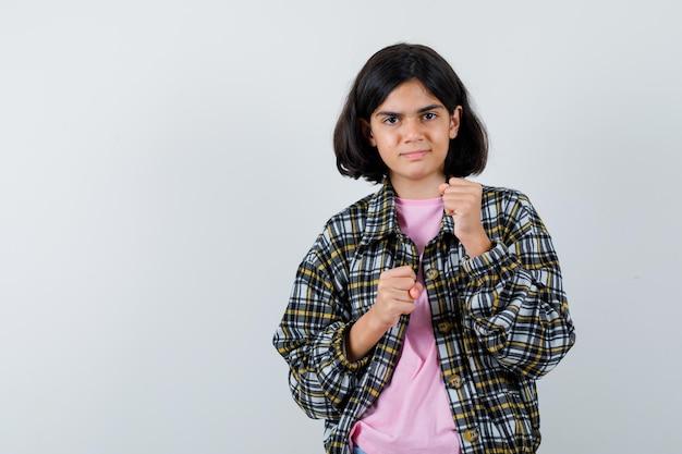 チェックシャツとピンクのtシャツでボクサーポーズで立っている若い女の子とかわいく見えます。