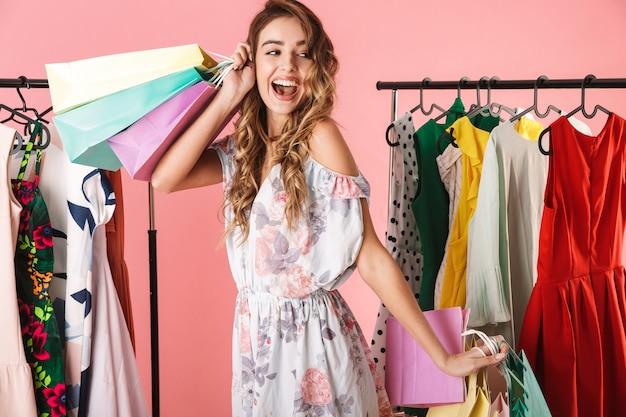 Молодая девушка стоит в магазине возле вешалки и держит разноцветные сумки для покупок, изолированные на розовом