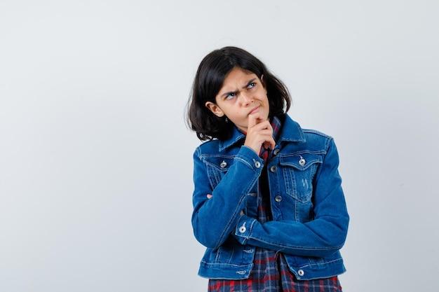 체크 셔츠와 진 재킷을 입고 생각에 잠긴 채 생각에 잠겨 있는 어린 소녀. 전면보기.