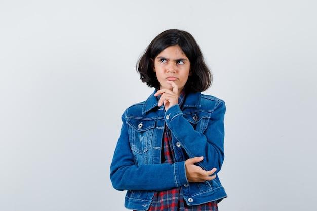 체크 셔츠와 진 재킷을 입고 생각에 잠긴 채 서 있는 어린 소녀