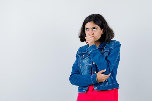 赤いtシャツとジージャンでポーズを考えて立っている少女と物思いにふける、正面図。