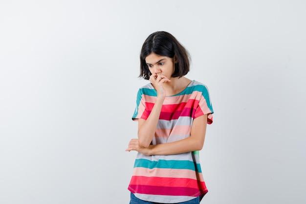 Молодая девушка, стоящая в задумчивой позе, положив руку на рот в красочной полосатой футболке и задумчиво, вид спереди.