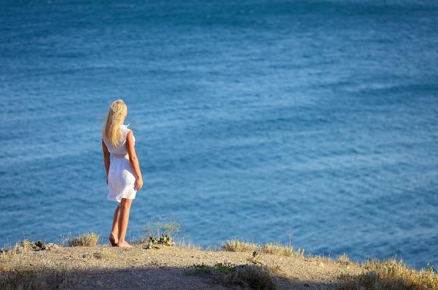 Молодая девушка стоит на скале и смотрит на море