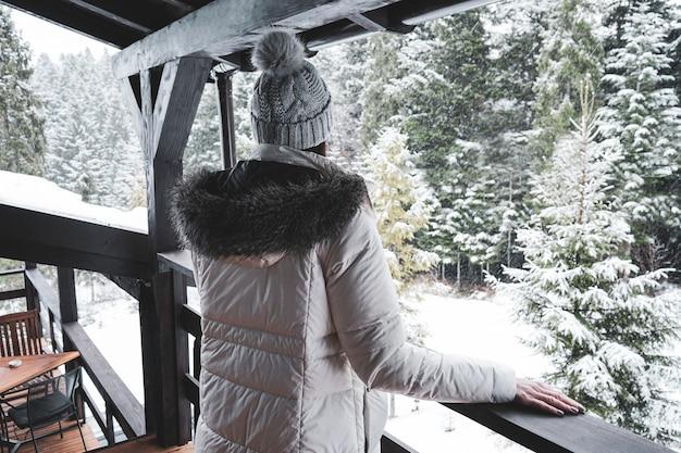 冬の森の景色を望むテラスに立っている若い女の子