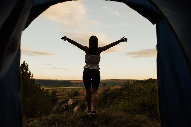 手を上げて崖の端に立って、自然の風景を楽しむ少女。