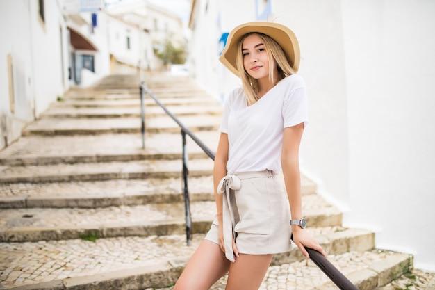 여름에 거리에서 돌 계단과 난간에 서있는 어린 소녀