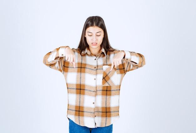 Giovane ragazza in piedi e rivolta verso il basso con il dito indice.