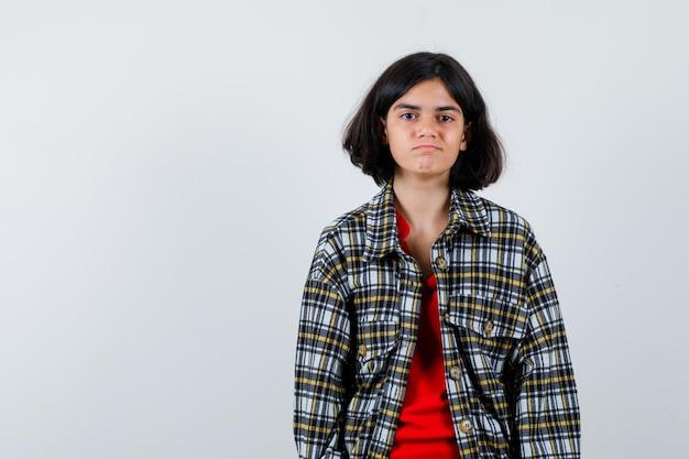 어린 소녀는 똑바로 서서 체크 셔츠와 빨간 티셔츠를 입고 카메라를 향해 포즈를 취하고 행복해 보입니다. 전면보기.