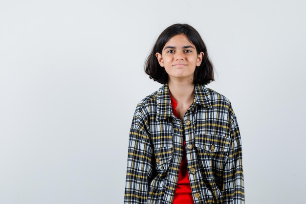 まっすぐ立って、チェックのシャツと赤いtシャツを着てカメラに向かってポーズをとって幸せそうに見える少女。正面図。