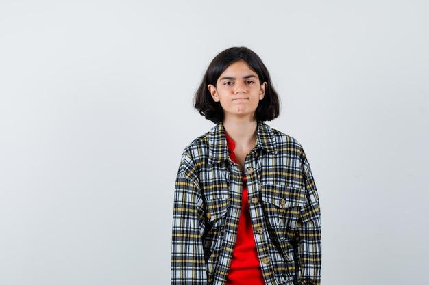 まっすぐ立って、チェックのシャツと赤いtシャツを着てカメラに向かってポーズをとって楽観的に見える少女。正面図。