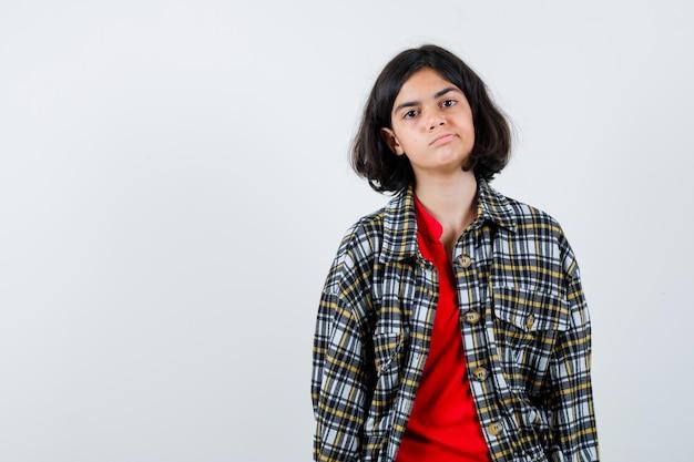 まっすぐ立って、チェックのシャツと赤いtシャツを着てカメラに向かってポーズをとって真剣に見える少女。正面図。