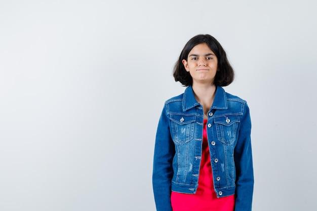 まっすぐ立って、赤いtシャツとジージャンでカメラに向かってポーズをとって幸せそうに見える少女。正面図。