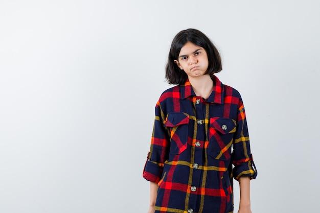 Giovane ragazza in piedi dritta, che soffia sulle guance e posa con una camicia a quadri e sembra seria. vista frontale.