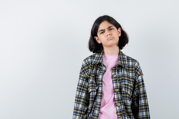 まっすぐ立って、顔をゆがめ、チェックシャツとピンクのtシャツを着てカメラに向かってポーズをとって、不機嫌そうに見える少女。正面図。