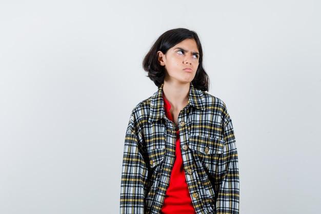 まっすぐ立って、目をそらし、チェックのシャツと赤いtシャツを着てカメラに向かってポーズをとって、イライラしている若い女の子。正面図。