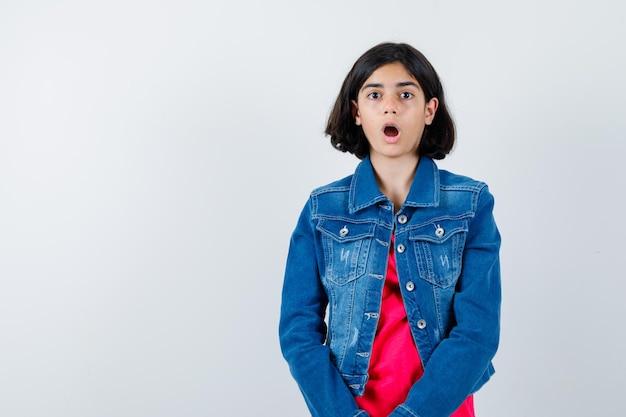 まっすぐ立って、口を開けて、赤いtシャツとジージャンでカメラに向かってポーズをとって、驚いて、正面図を見て若い女の子。
