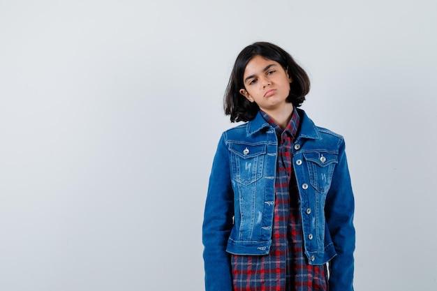 Giovane ragazza in piedi dritta e in posa alla macchina fotografica in camicia a quadri e giacca di jeans e sembra carina. vista frontale.