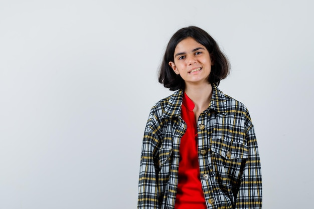 Young girl standing straight and posing at camera in checked shirt and red t-shirt and looking happy. front view.